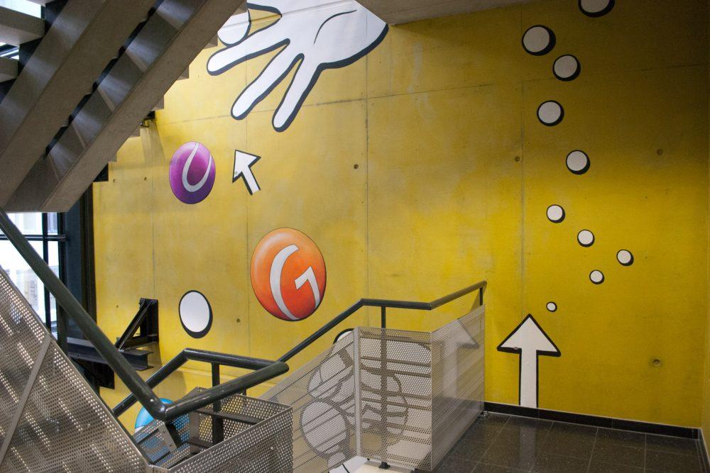 Blick vom 1.OG auf Wandbild nach oben mit orangenem und violetterm Ball